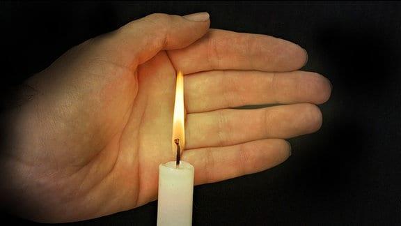 Eine Hand hinter einer brennenden Kerze