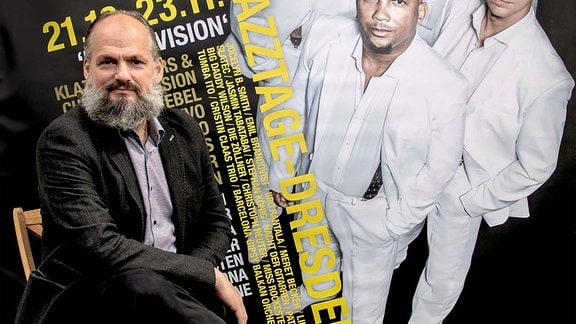 Der Intendant der Jazztage Dresden und Bassist der Klazz Brothers Kilian Forster vor dem Plakat der Jazztage Dresden 2020.