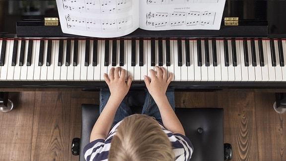Ein 4 jahre alter Junge spielt Klavier.