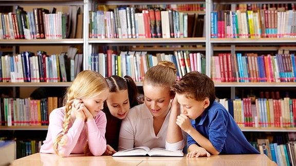 Kinder lesen in einem Buch.