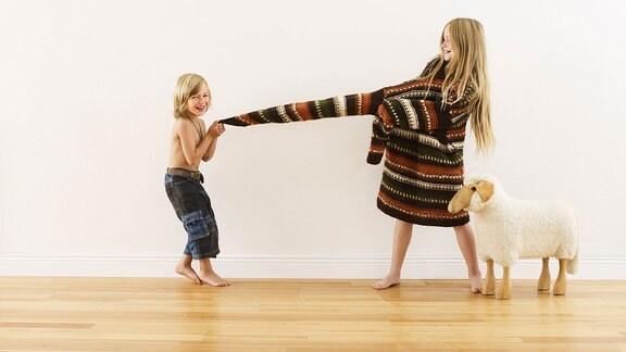 Junge zieht am Pullover eines Mädchens, daneben steht ein Spielzeugschaf