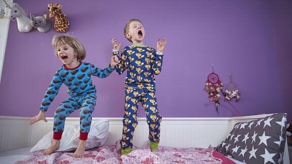 Kinder in Schlafanzügen springen auf einem Bett herum.