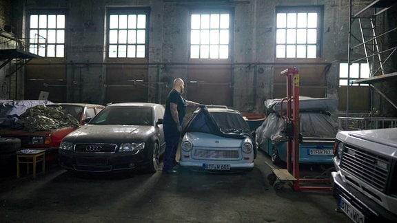 Mann mit Bart in einer Garage neben alten Autos