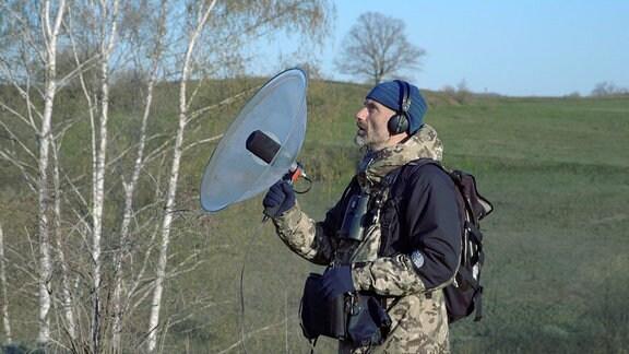Ein Mann mit Kopfhörern lauscht in die Natur