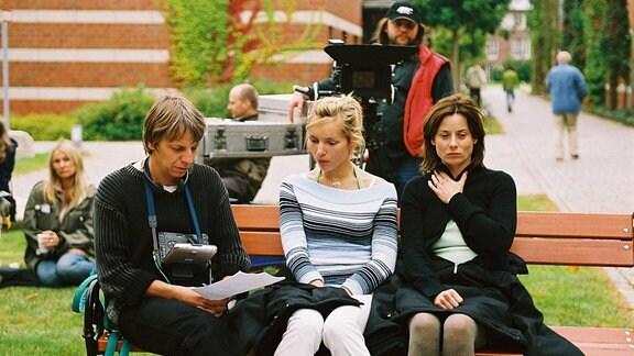 Andreas Dresen mit Nadja Uhl und Inka Friedrich auf einer Bank am Filmset