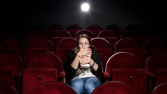 Eine Frau sitzt alleine in einem Kinosaal, schaut einen Film und gruselt sich