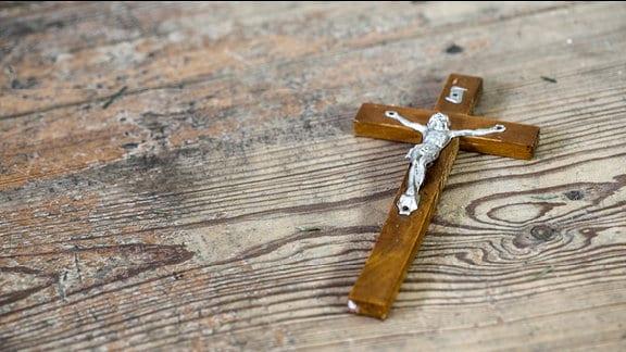 Ein Kreuz liegt auf einem Tisch.