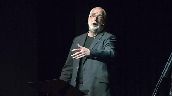 Ein Mann steht auf einer Bühne und spricht zum Publikum.