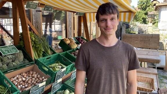 Ein junger Mann in braunem T-Shirt steht unter einer Markise vor grünen Kisten voller Gemüse