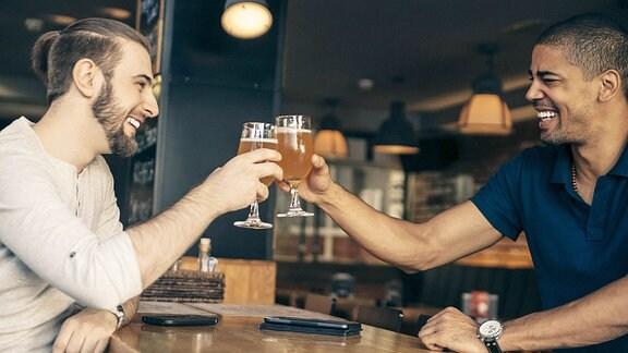 Zwei junge Männer mit Bier in einer Kneipe.