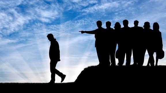 Symbolbild: Eine Gruppe Menschen weißt eine Person aus