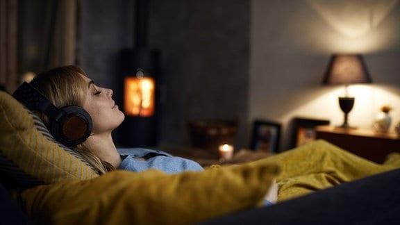 Eine Frau liegt mit Kopfhörern auf dem Sofa