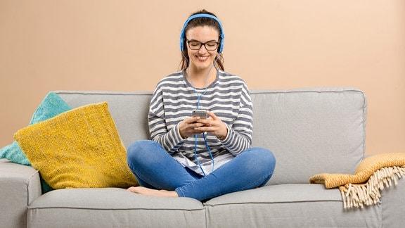 Junge Frau trägt Kopfhörer und sitzt auf einem Sofa