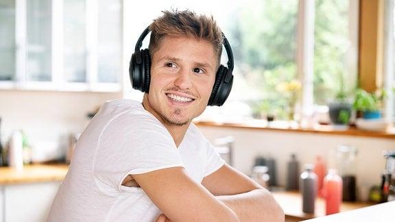 Junger Mann sitzt mit Kopfhörern in der Küche.