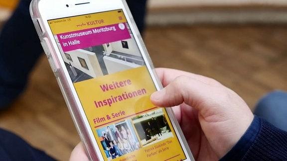 Finger scrollt in der MDR KULTUR App auf dem Smartphone.