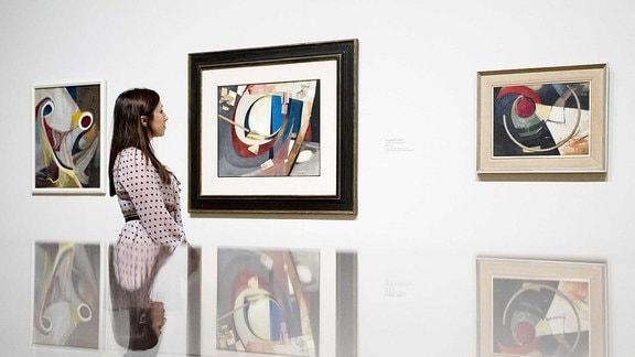 Eine Frau schaut sich in einer Galerie Werke von Kurt Schwitters an.