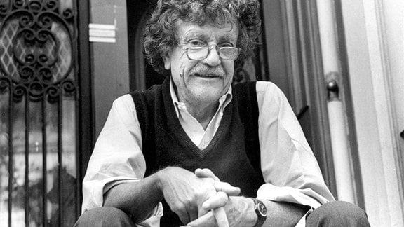 Ein Mann mit lockigem Haar und Brille sitzt auf einer Treppe vor einem Gebäude und schaut lächelnd in die Kamera.