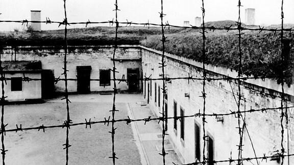 Blick durch Stacheldraht auf die Gebäude des Konzentrationslagers Theresienstadt