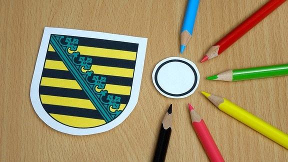 Neben dem Wappen von Sachsen sind symbolträchtig sechs Buntstifte in den Farben der unterschiedliche nParteien angeordnet