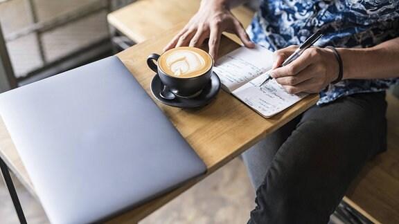 Ein Mann sitzt an einem Tisch, auf dem ein Laptop und eine Tasse Kaffee stehen, und schreibt in ein Notizbuch.