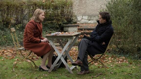 Eine Frau und ein Mann sitzen im Freien an einem Gartentisch.