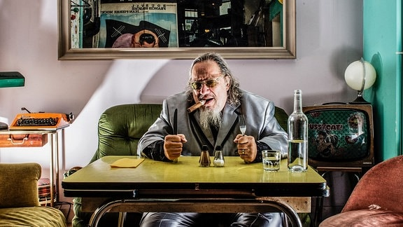 """Larry """"Ratso"""" Sloman sitzt mit Zigarre am Tisch"""