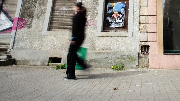 Eine Frau geht an leerstehenden Häusern in Dresden vorüber.