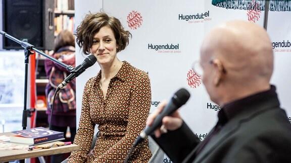 Eine Frau und ein Mann mit Mikrofonen bei einem Gespräch in einer Buchhandlung.