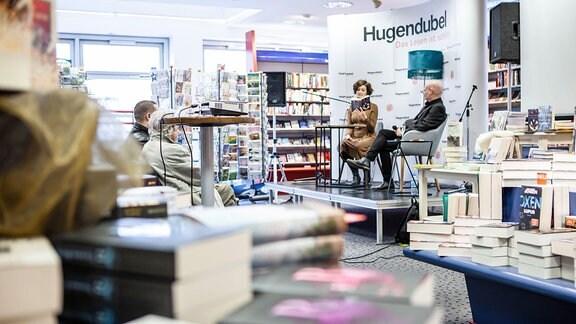 Zwei Personen auf einer Bühne in einer Buchhandlung lesen aus Büchern vor.
