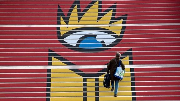 Eine Frau steigt in der Glashalle der Neuen Messe in Leipzig eine Treppe mit dem Logo der Leipziger Buchmesse hinauf.