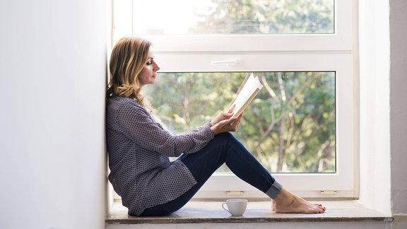 Eine Frau sitzt an einem Fenster und liest.
