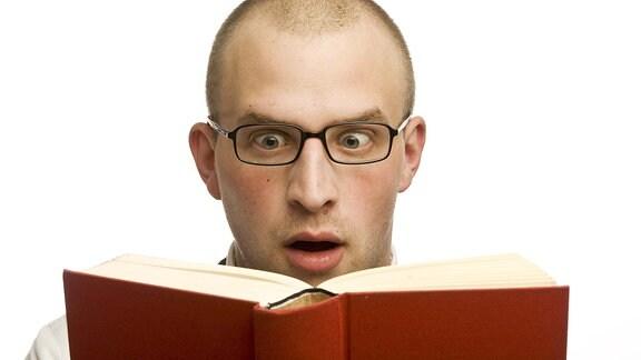 Ein Mann mit Brille sieht in ein Buch