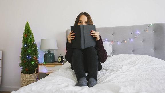 Eine Frau sitzt in einem Bett und schaut über ein Buch.