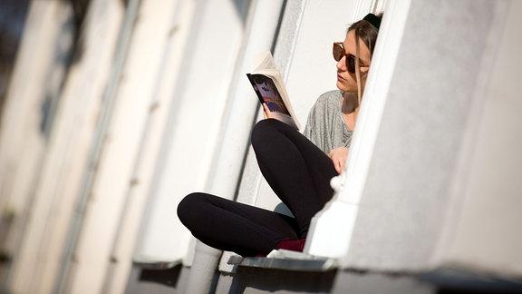 Eine Frau sitzt auf der Fensterbank im Sonnenschein und liest ein Buch.