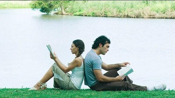 Eine Frau und ein Mann sitzen Rücken an Rücken und lesen