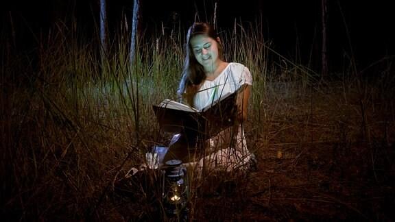 Eine Frau liest in einem Buch.