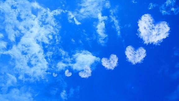 Ein blauer Himmel mit Herz-Wolken.