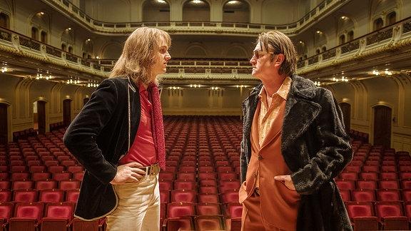 Der junge Lindenberg mit einem Manager auf einer Bühne vor dem leeren Saal eines Theaters.