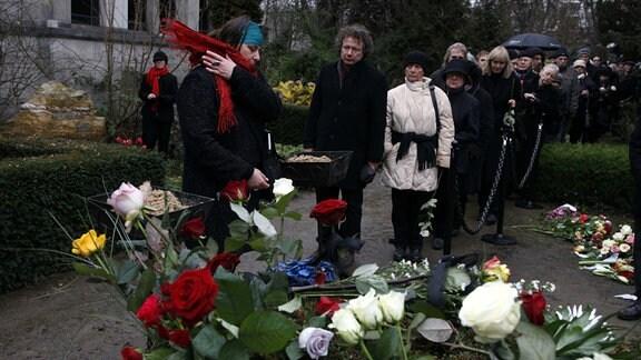 Beisetzung der Schriftstellerin Christa Wolf, sie verstarb im Alter von 82 Jahren und wurde am 13.12.2011 auf dem Dorotheenstädtischen Friedhof in Berlin-Mitte beerdigt - Schriftstellerin Annett Gröschner trauert am Grab, dahinter Ingo Schulze
