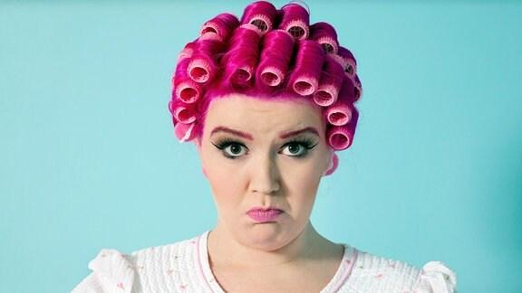 Eine pink gefärbte Frau mit Lockenwicklern in den Haaren.