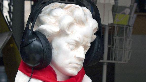 Beethoven-Büste mit modernen Kopfhörern und einen rotem Schal.