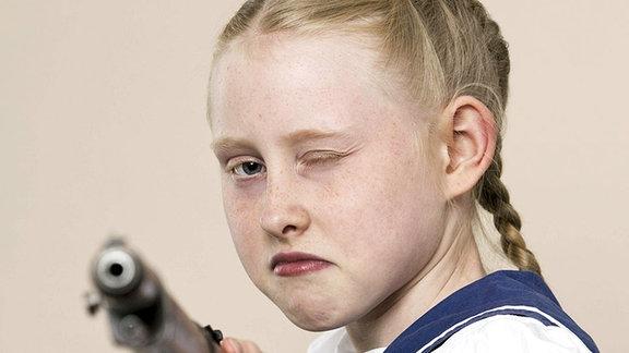 Ein Mädchen in einem Segleroutfit zielt mit einem Gewehr auf die Kamera.