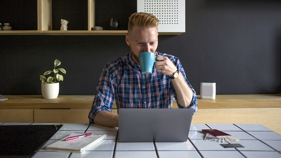 Mann arbeitet zu Hause an einem Laptop und trinkt dabei einen Kaffee.