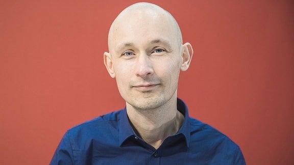 Matthias Senkel vor rotem Hintergrund.
