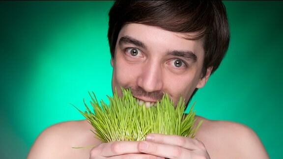 Junger Mann beisst in ein Büschel frisches grünes Gras.