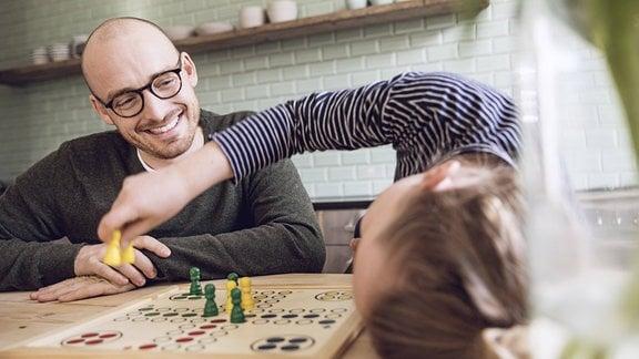 Vater und Tochter beim 'Mensch ärgere Dich nicht'_Spielen