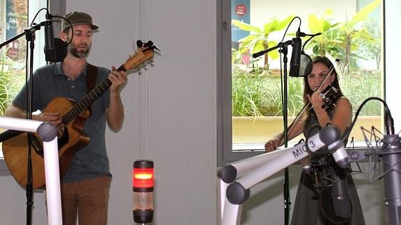 Ein Mann mit Gitarre und eine Frau mit Geige spielen in einem Hörfunkstudio