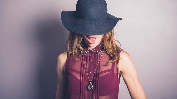 Junge Frau trägt einen Hut und eine durchsichtige Bluse