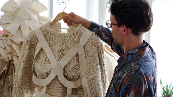 Modedesigner Kaur Hensel hält Kleidungsstück