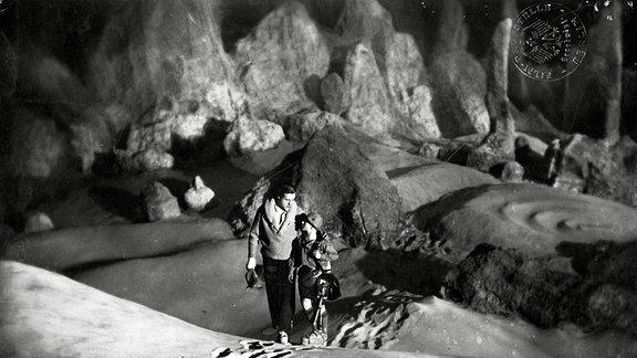 Szene aus Frau im Mond - Ein Mann und eine Frau laufen auf der Mondoberfläche entlang.